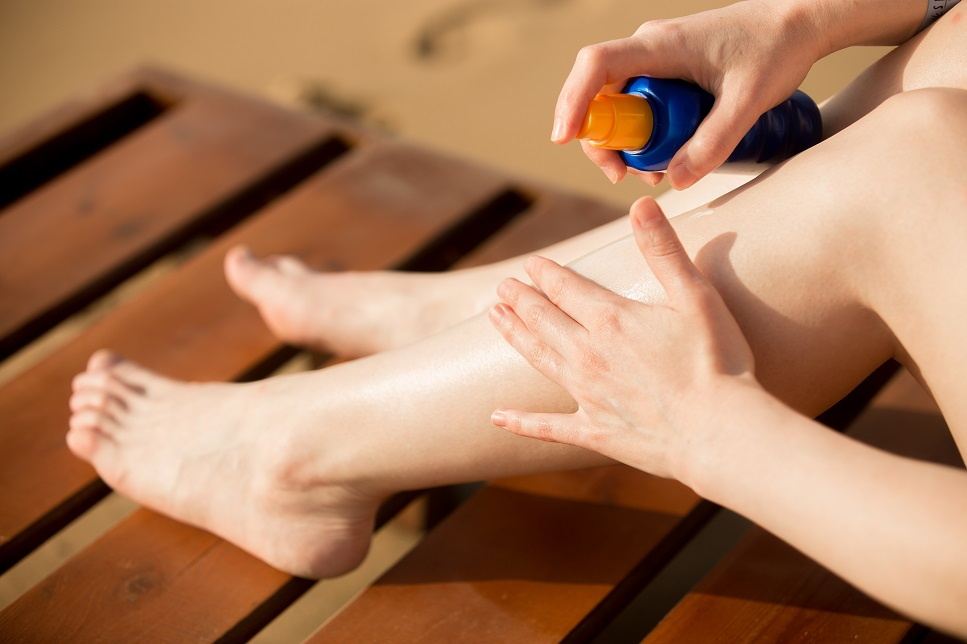 A woman putting sunscreen on her legs and feet